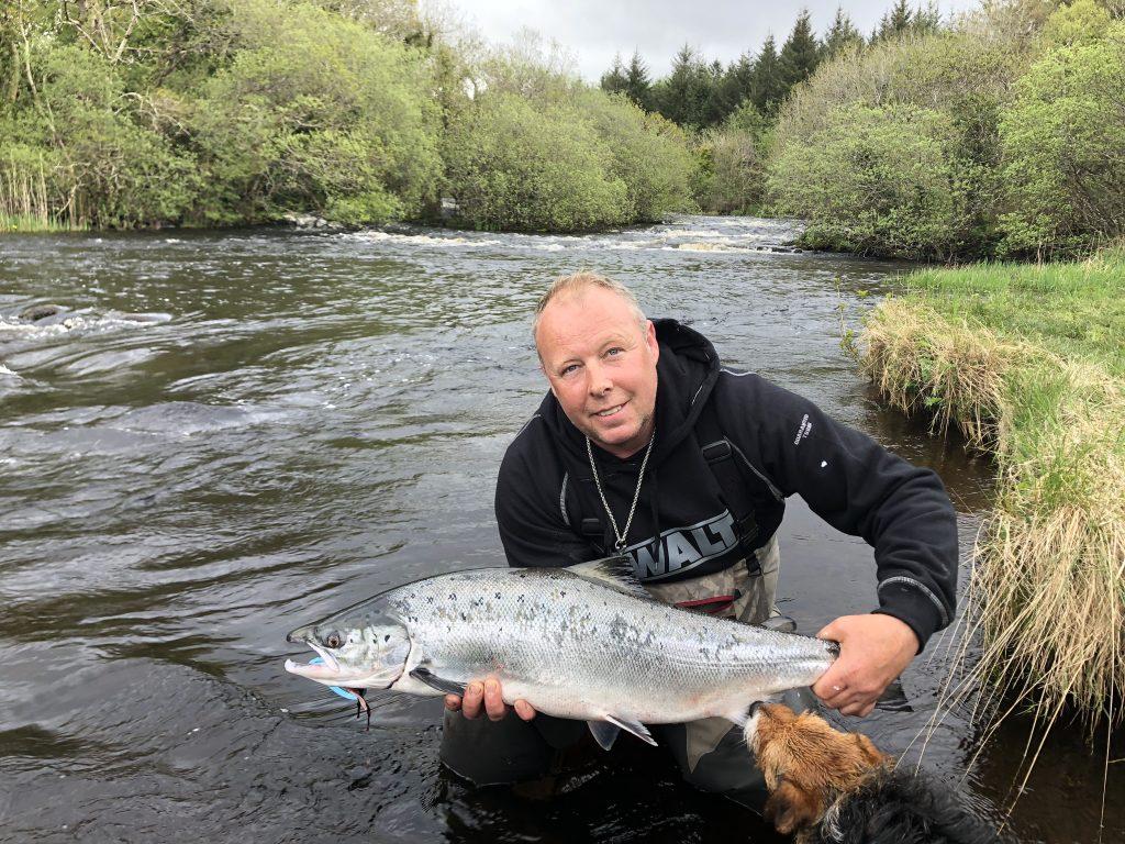 Mark Barbou's bijna twaalf pond zware zalm. De vis heeft de interesse van de zeldzame Drowes Water Terrier. Pas op, deze kan overal langs de rivier opduiken en er met je vis vandoor gaan!