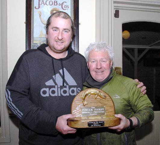 Barry Darby, zoon van de overleden Finian, overhandigt de trofee aan Mick Flanagan.